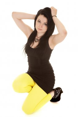 Woman black dress yellow legs kneel