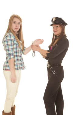Woman cop handcuff woman looking