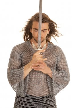man chain mail sword front of face eyes closed