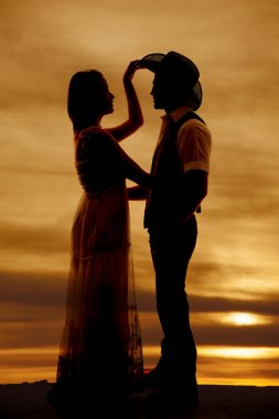 cowboy couple silhouette her hand his hat