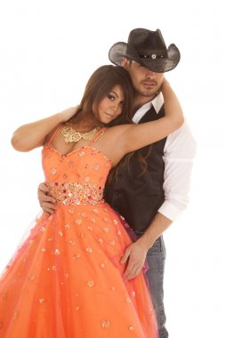 cowboy woman orange dress reach back to neck looking