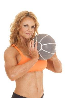 Mature woman orange bra medicine ball close