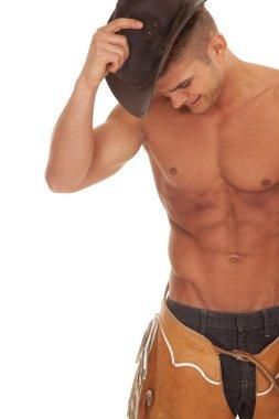 man no shirt chaps hold hat on head close