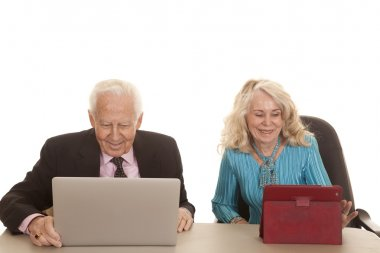 elderly couple business computers look down
