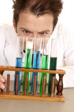 Mad scientist look at test tubes