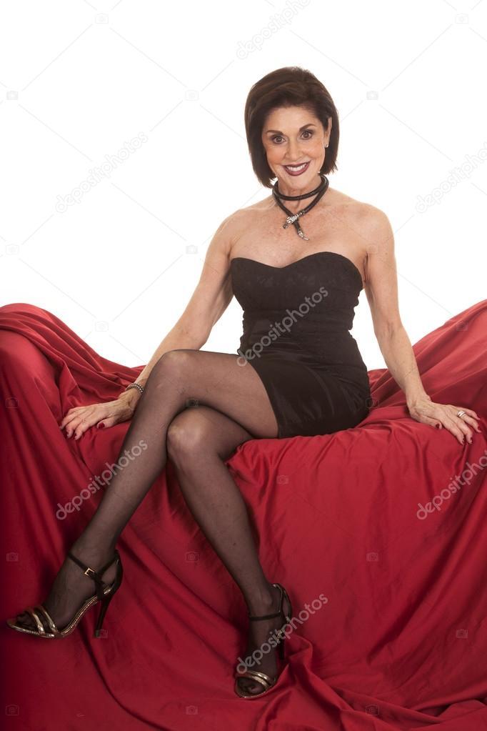 3998fc386fba Una donna anziana con un sorriso sul suo viso seduto su un divano rosso —  Foto di ...