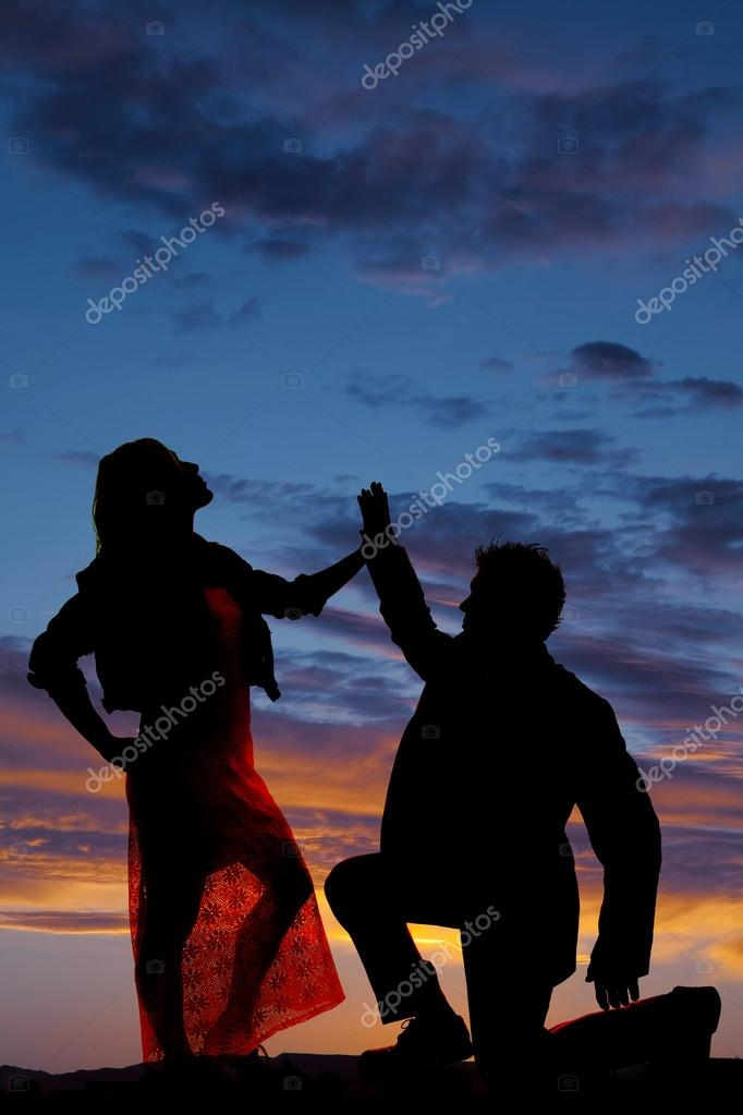 silhouette man kneel touch womans hand