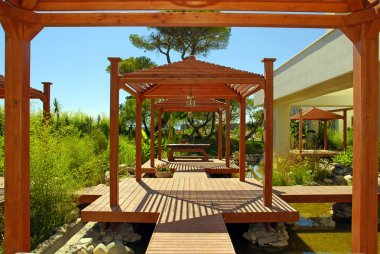 Wood pavilion, deck and tropical plants in summer resort