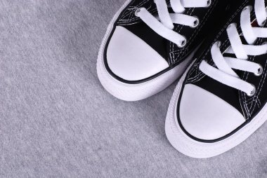 Black canvas sneakers on grey textile background