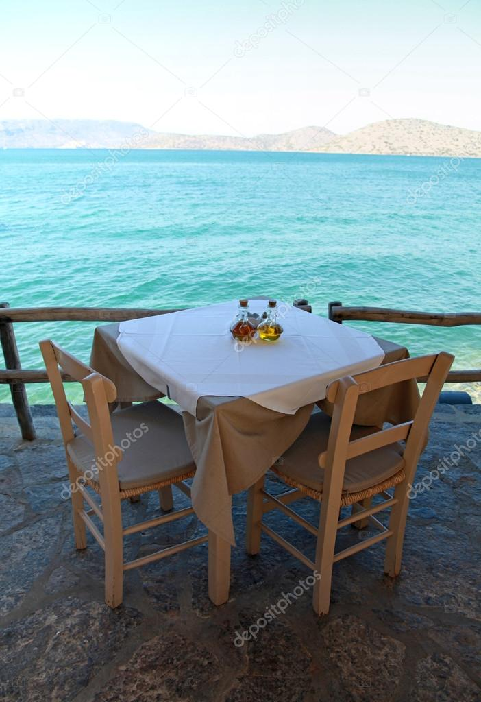 Greek outdoor restaurant with Mediterranean sea view(Crete, Greece)
