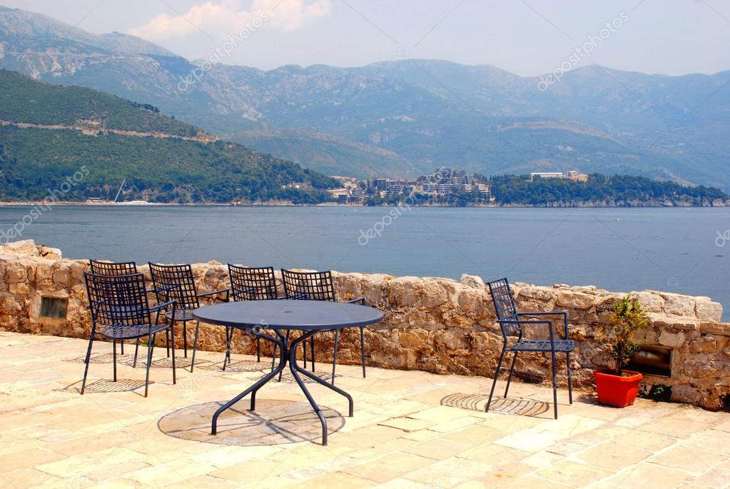 Blue iron chairs and table on stone terrace with sea view