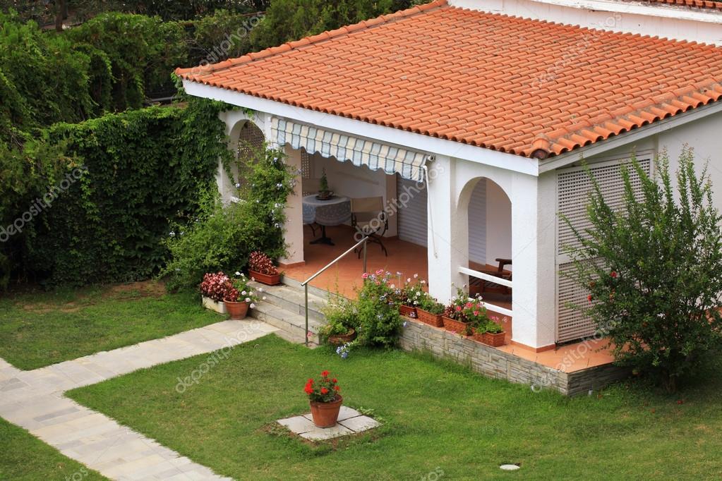 Hermosa casa blanca con peque a terraza en el jard n for Tejabanes para terrazas