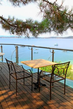 Table and iron chairs on terrace with sea view (Greece)