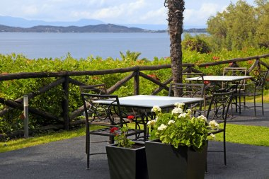 Tables and iron chairs on terrace with sea view (Greece)