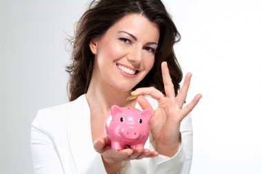 Young beautiful woman standing with piggy bank money box