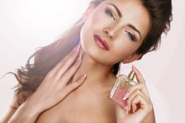 Closeup of a beautiful woman applying perfume