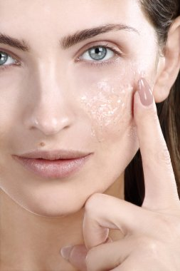 Beautiful woman applying scrub treatment on face