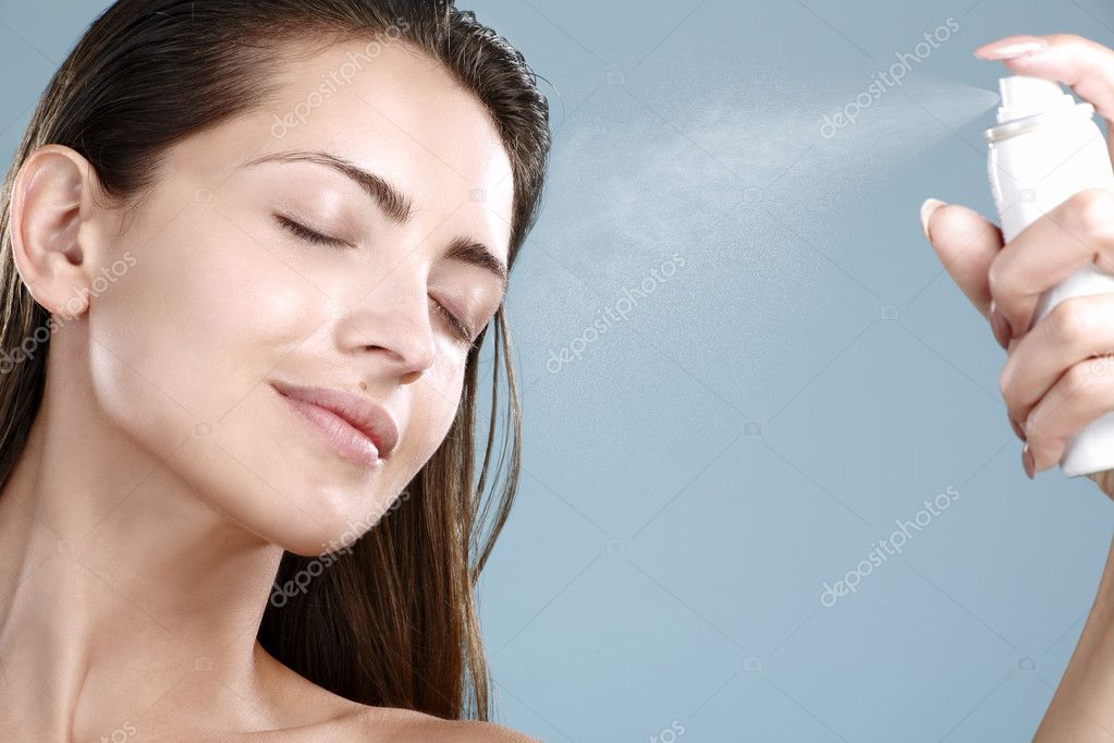 Beautiful woman applying spray  water treatment on face