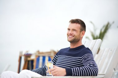 Handsome Man Sitting and Smiling Outdoors