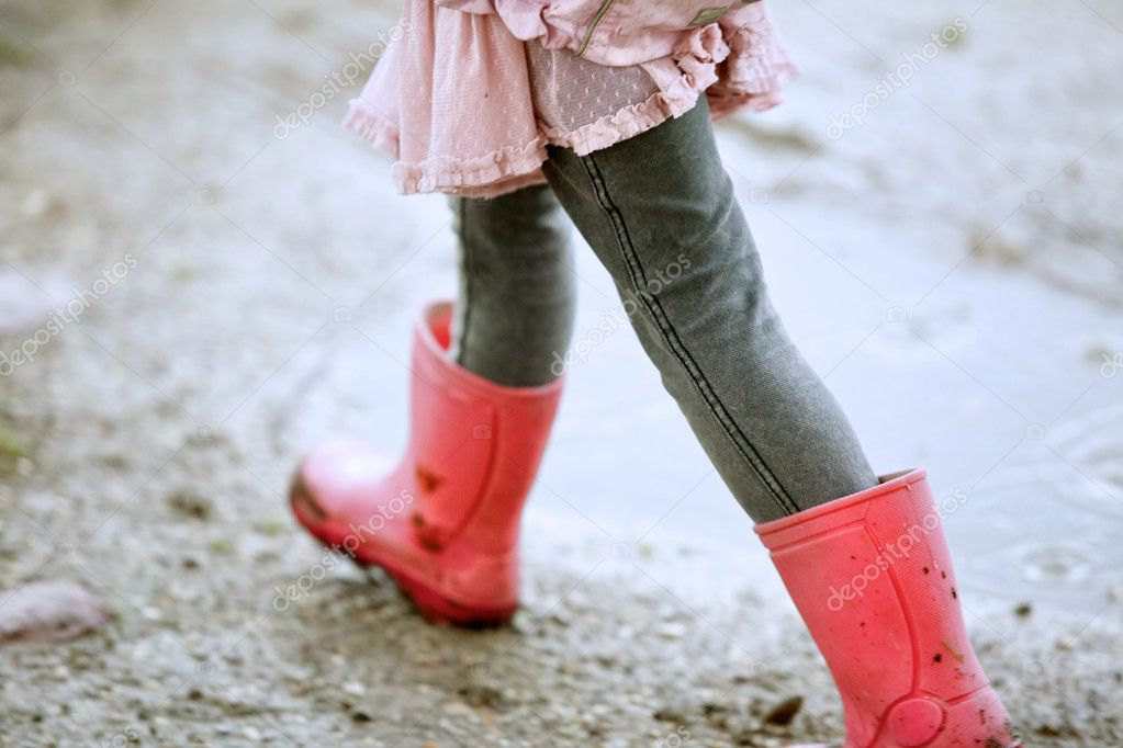 Little Girl Walking Outdoors with Red Boots
