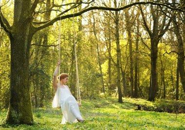 Elegant bride in white wedding dress sitting alone on swing outdoors