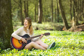 Fotografie Portrait of a beautiful young woman smiling and playing guitar outdoors