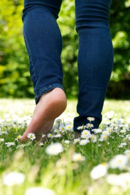 Young woman walking barefoot on green grass in the park