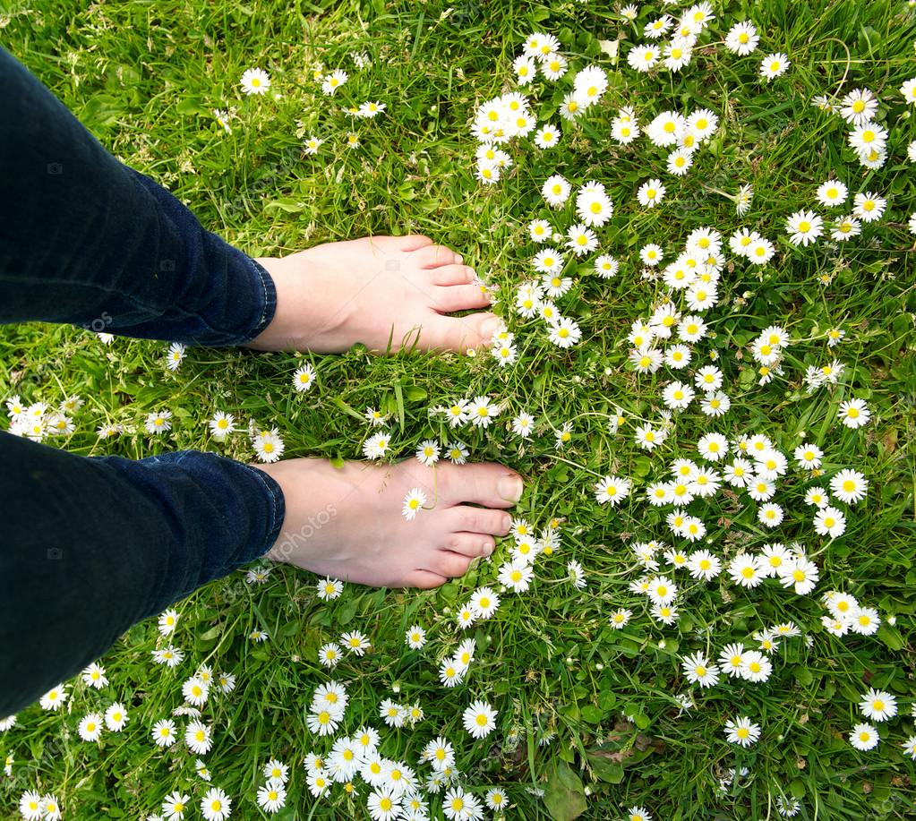 Female standing barefoot on green grass and white flowers