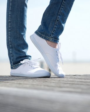 Woman legs in comfortable white shoes standing outdoors