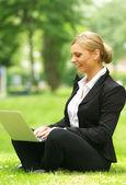 šťastné ženy sedí na trávě s notebookem