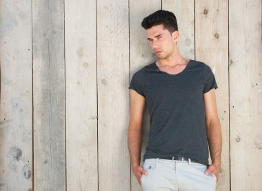 Good looking young man standing outdoors against wall