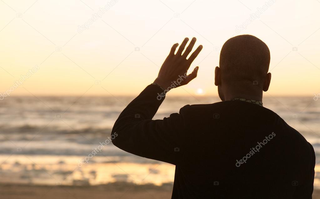Man waving at the sunset
