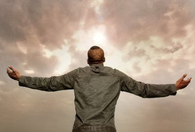 Man with outstretched arms looking at the sky