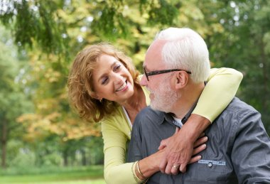 Happy older couple smiling and looking at each other outdoors