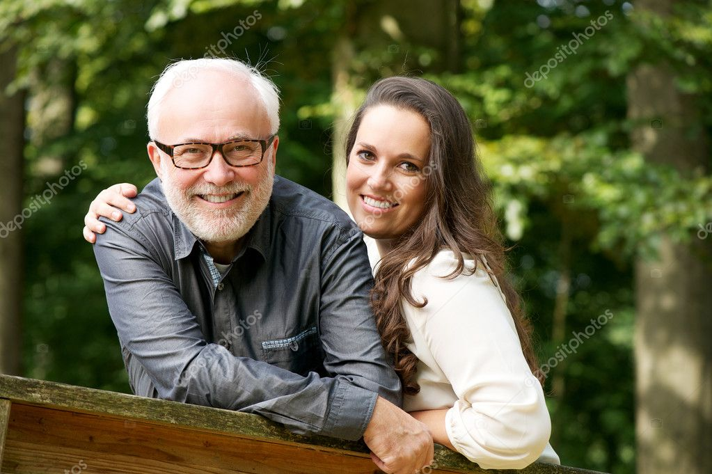 Happy mature man smiling with young woman