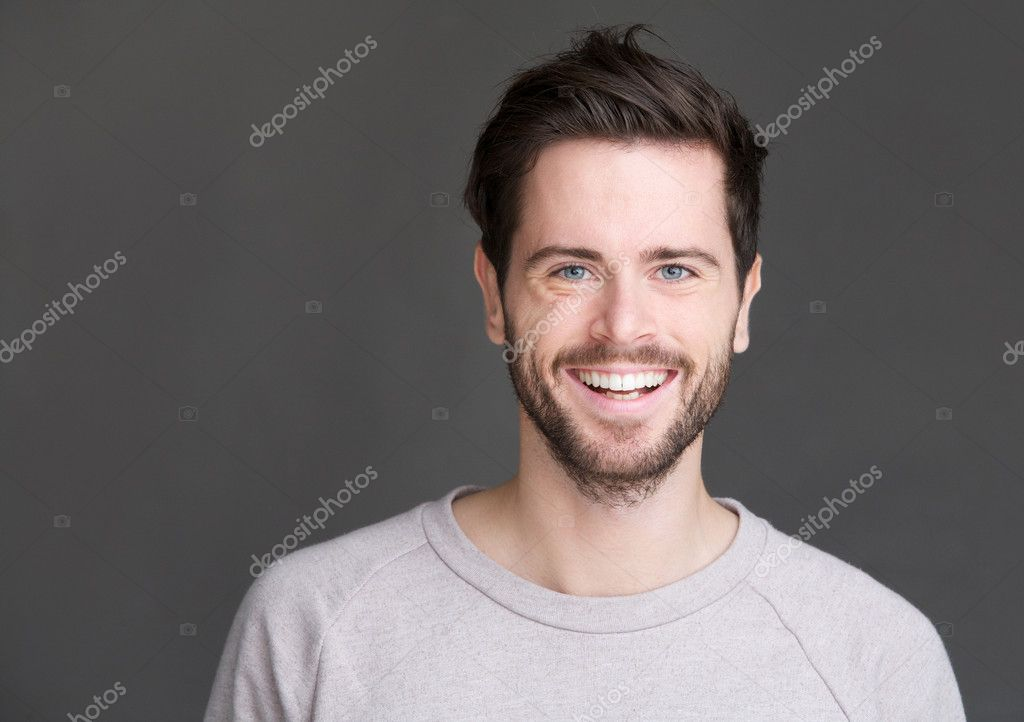 Portrait of a happy young man smiling on gray background