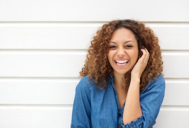 Portrait of a beautiful woman laughing with hand in hair