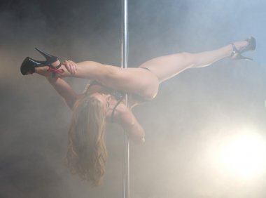 Beautiful young woman pole dance with legs open