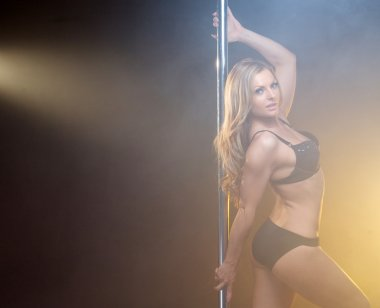 Beautiful young pole dancer with blond hair