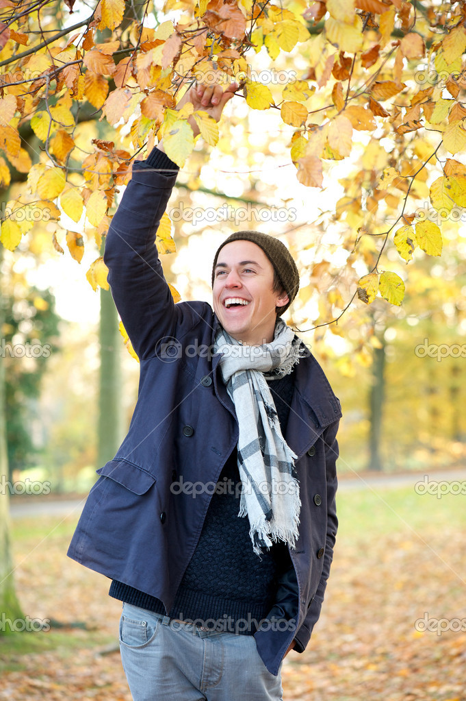 Portrait of a cheerful young man laughing outdoors