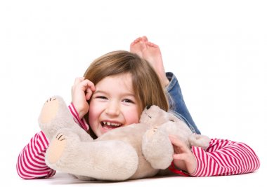 Young girl laughing with teddy bear