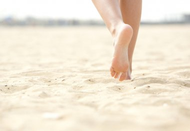 Woman barefoot walking on beach