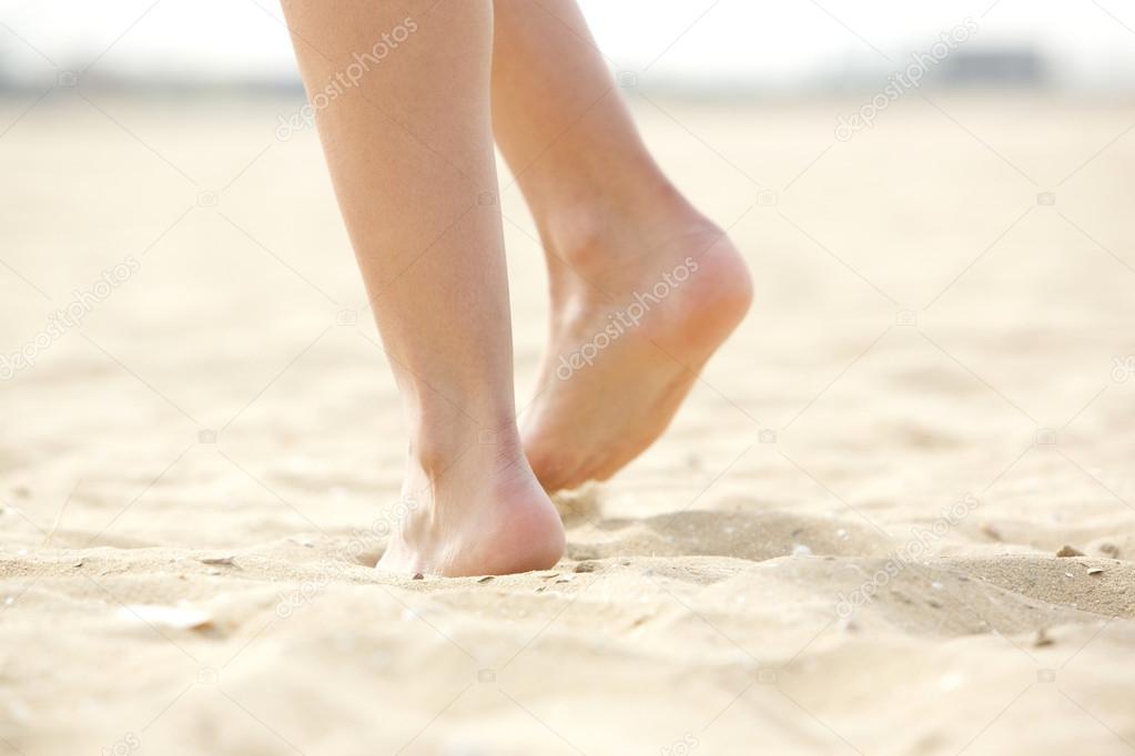 Woman walking barefoot on sand