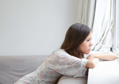 Young woman sitting alone looking out window