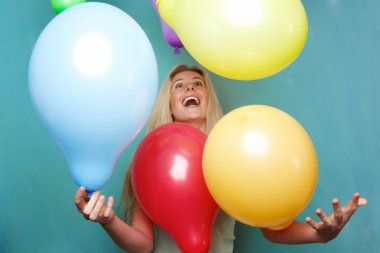 Blond woman playing with balloons