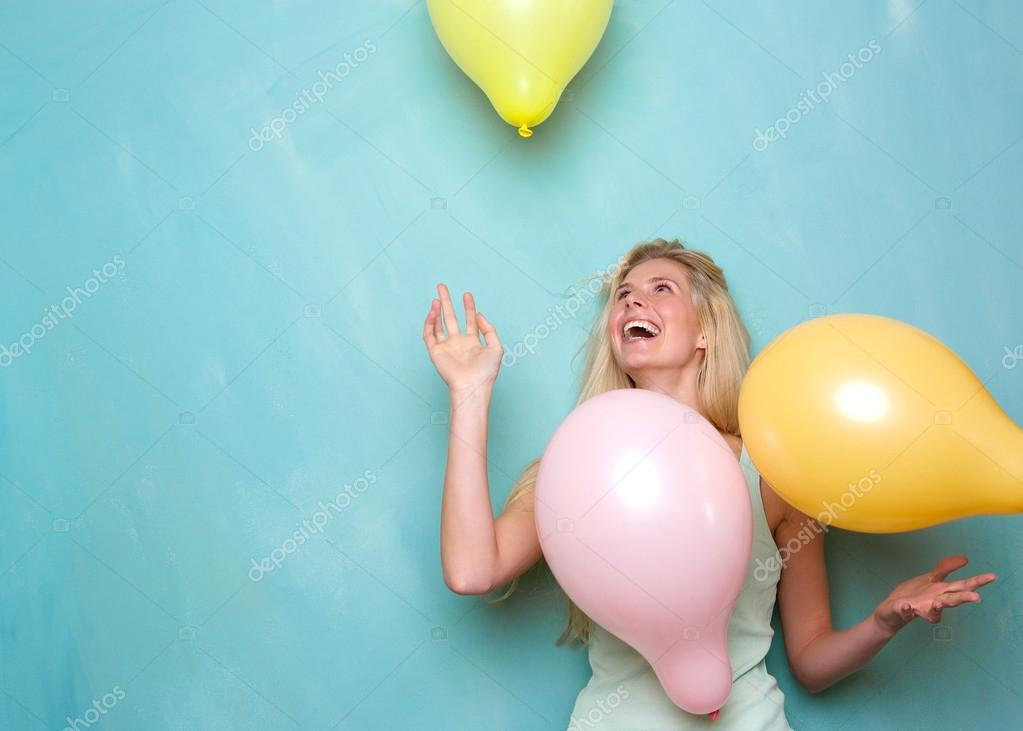 Young woman smiling and playing with balloons
