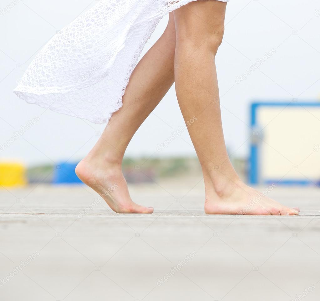 Young woman walking barefoot outdoors