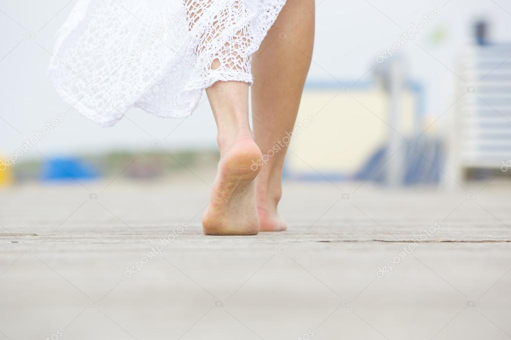 Low angle barefoot woman walking away