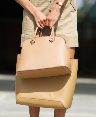 Woman holding two brown leather handbags