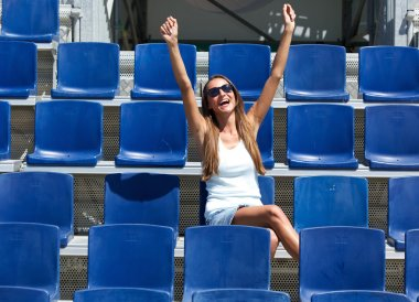 Young woman cheering with arms raised